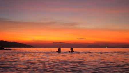 Silhouette of father and little son bathing in sea at beautiful sunset. Travel holiday concept. Stock Photo
