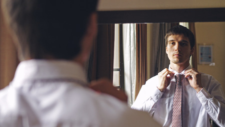 Handsome man in white shirt stands by the mirror tying a tie 写真素材