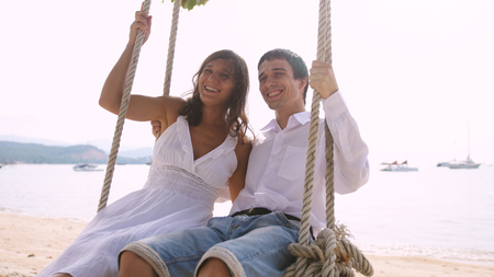 Young happy smiling pretty couple on a swing at the tropical beach against the sea Stock fotó