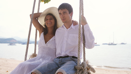 Young happy couple on a swing at the tropical beach against the sea