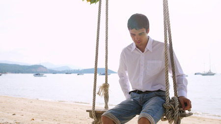 Handsome businessman in white shirt swinging on hammock on exotic tropical beach