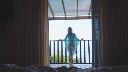 Beautiful girl stands on balcony with amazing sea view in her vacation.