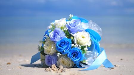 Boeket bloemen op het strand wit zand tropisch Paradijseiland op zeewater oceaan achtergrond en bewolkte hemel Stockfoto