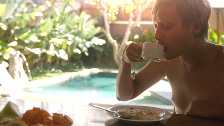 Young man drinking coffee during breakfast sitting on his villa on swimming pool on the background. vacation concept
