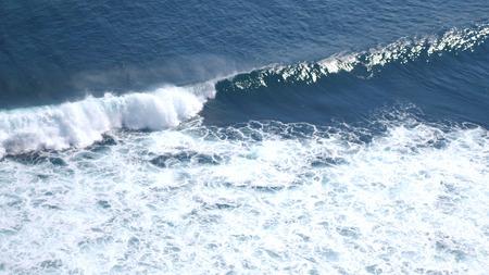 Aerial drone view of foaming waves in ocean