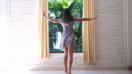 Girl in dress unveil the curtains in the morning Stock Photo