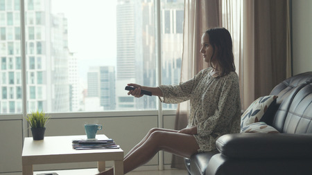 Young beautiful brunette woman sits on the sofa puts her feet on table and relaxes. The girl watches TV by the window with building on the background holds remote controller in her hand Imagens