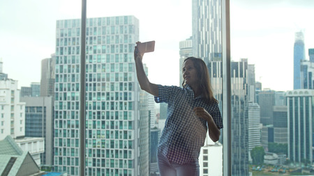 Happy brunette woman taking selfie photo with cellphone by window at apartment with beautiful urban view.