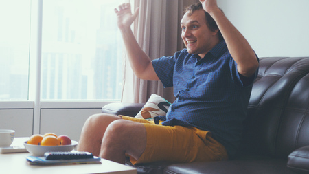 Handsome exited man watching a football match in his living room by the window 免版税图像