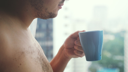 Close up of young handsome man hand with a cup of coffee looks at city towers from a window.