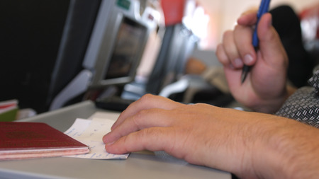 Passenger with passport is filling in the migration or arrival cards in the plane while flight Banco de Imagens