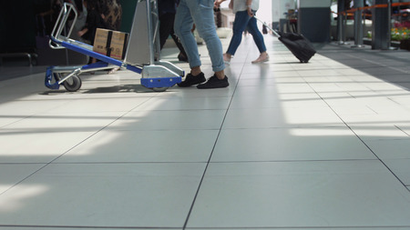Close up of unrecognizable people with baggages walking in terminal airport. View on the floor