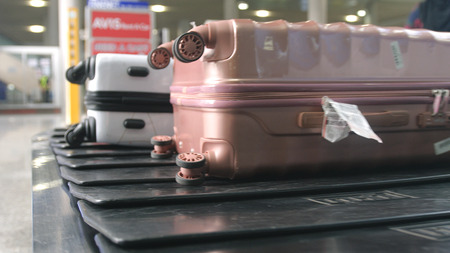 Airport baggage claim with luggage spinning around conveyor 写真素材