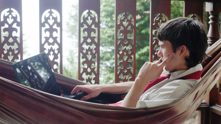 Young businessman using laptop computer, resting in a hammock