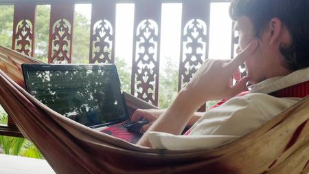 Giovane uomo d'affari serio che usa il computer portatile, riposa su un'amaca Archivio Fotografico