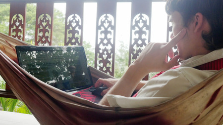 Young serious businessman using laptop computer, resting in a hammock Archivio Fotografico