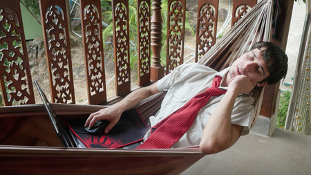 Man sleeping with laptop computer, resting in a hammock