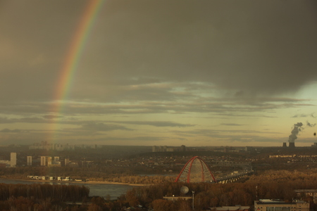 Bugrinsky bridge over the Ob river in Novosibirsk against cloudy sky with a bright rainbow