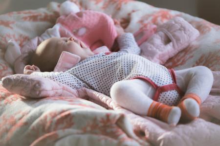 Süßes kleines Baby, das auf dem Rücken liegt, gähnt auf dem weichen Bezug Standard-Bild