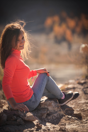 Beautiful young smiling woman enjoys the beauty Valley along the hiking trail posing on the rock on sunny day in Altai