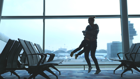 Mother embracing son and spinning around loving family waiting for flight