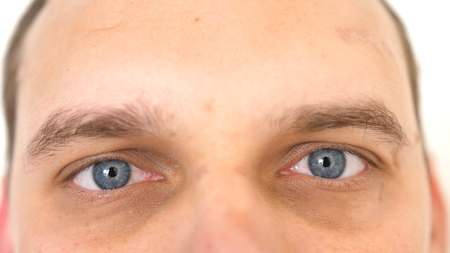 Close up of a male eyes. Detail of a blue eyes of a man looking at camera.