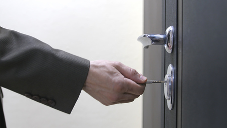 Close up of a man hand unlocks a houses door with key Stockfoto