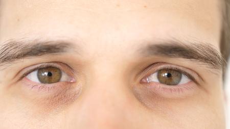 Cerca de los ojos masculinos. Detalle de los ojos marrones de un hombre mirando a la cámara. Foto de archivo