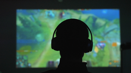 Back view of silhouette of a young man plays video games in dark room watches a movie in headphones