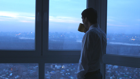 Young businessman drinking tea and admire view from window in the evening in office 写真素材