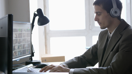 Successful businessman in headphones sitting at his desk, working on a computer by the panoramic Window.