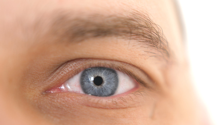 Close up of a male eye. Detail of a blue eye of a man looking at camera