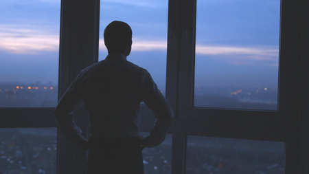 Businessman stands near the window and looks on night city background.