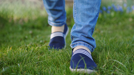 Young woman in blue sneakers goes on a meadow