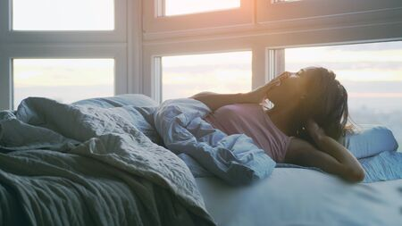 Beautiful happy brunette woman lying on the bed yawning in the morning in her roo during sunrise Фото со стока