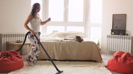 Young woman dancing with vacuum cleaner doing chores cleaning house having fun silly dance listening to music wearing headphones enjoying carefree weekend morning at home