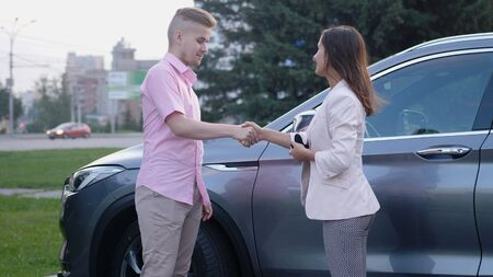 Business lady receiving car key on the background of a car, successful deal of buying the car