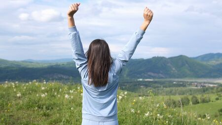 Young woman standing on mountains nature background amazing landscape and raising up her hands