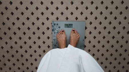 Female feet standing weighing scales in a room. Top of view