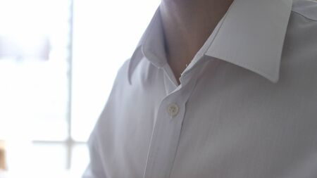 Young man dressing close-up white shirt