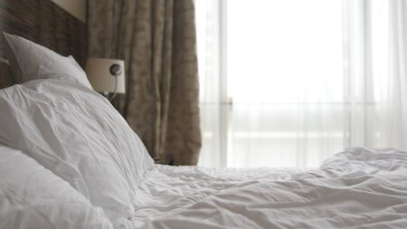white bedding sheets and pillow in apartment