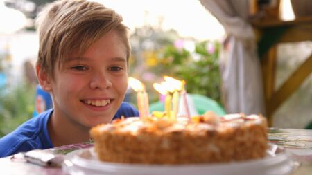 Happy child blows out candles on a birthday cake. Close up. slow motion.