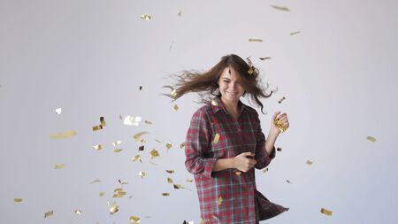 Beautiful woman dancing and throwing gold confetti. 写真素材