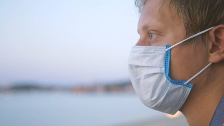 Young man in medical mask meditates on the beach. Coronavirus epidemic