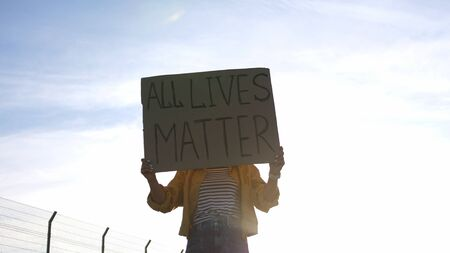 Young protesting woman holds a poster - All Lives Matter