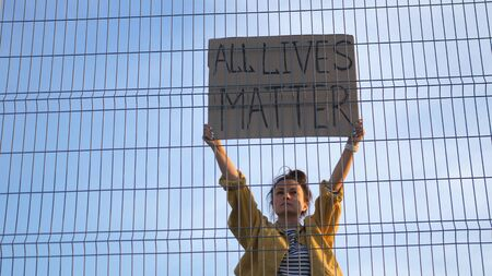Young protesting woman standing behind the fence holds a poster - All Lives Matter Standard-Bild