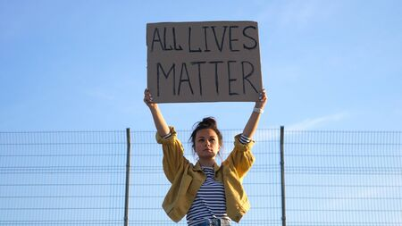 Young protesting woman holds a poster over her head - All Lives Matter Standard-Bild