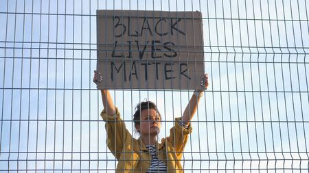 Young protesting woman standing behind the fence holds a poster - Black Lives Matter Standard-Bild
