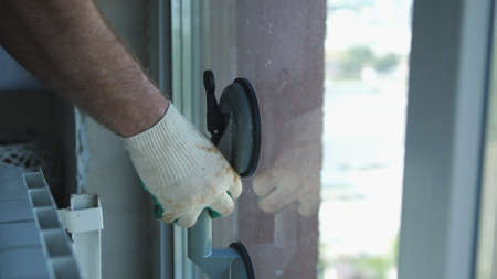 Worker put window sash into new installed frame. Close up of hand