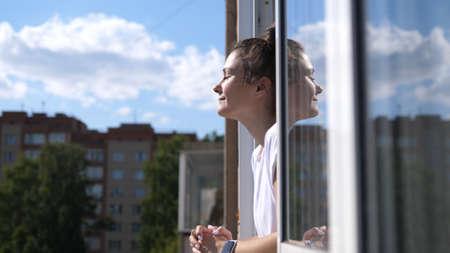 Cheerful girl breathes on the balcony enjoying the sun